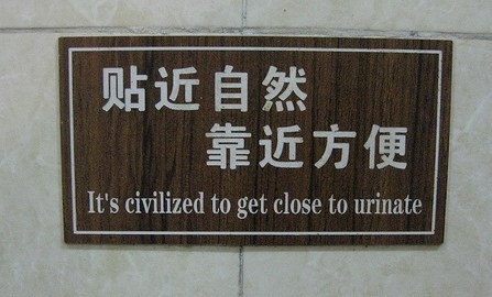 """Poorly translated English sign in China that reads """"It's civilized to get close to urinate"""""""