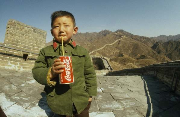 A Chinese boy drinking a Coca-cola on the Great Wall of China