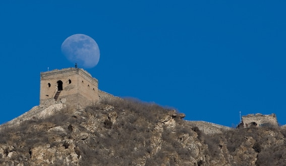 A view of the Great Wall with the moon in the background