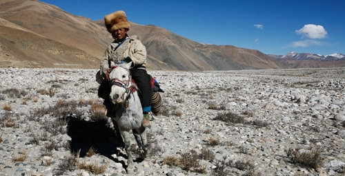 tibetan man on horse traveling tibetan plain