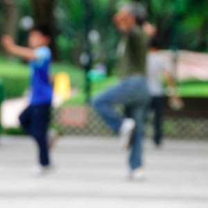 Blurred image of two Chinese people doing Tai Chi outdoors