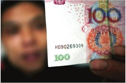 A person checking a Chinese 100 yuan note to see if it's a fake