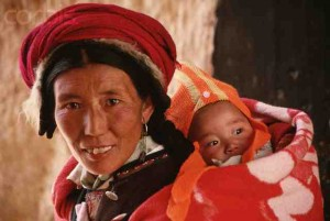 A rural Chinese woman carrying a baby on her back