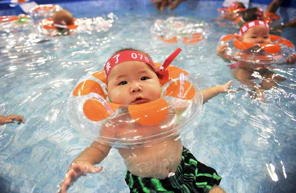 A Chinese baby with a floaty in the water.