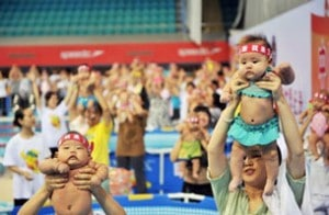 Chinese babies held up by their parents during an event