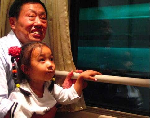 A Chinese man and daughter riding a bullet train