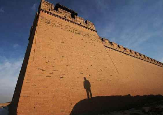 A modern city wall in China with the silhouette of a traveler