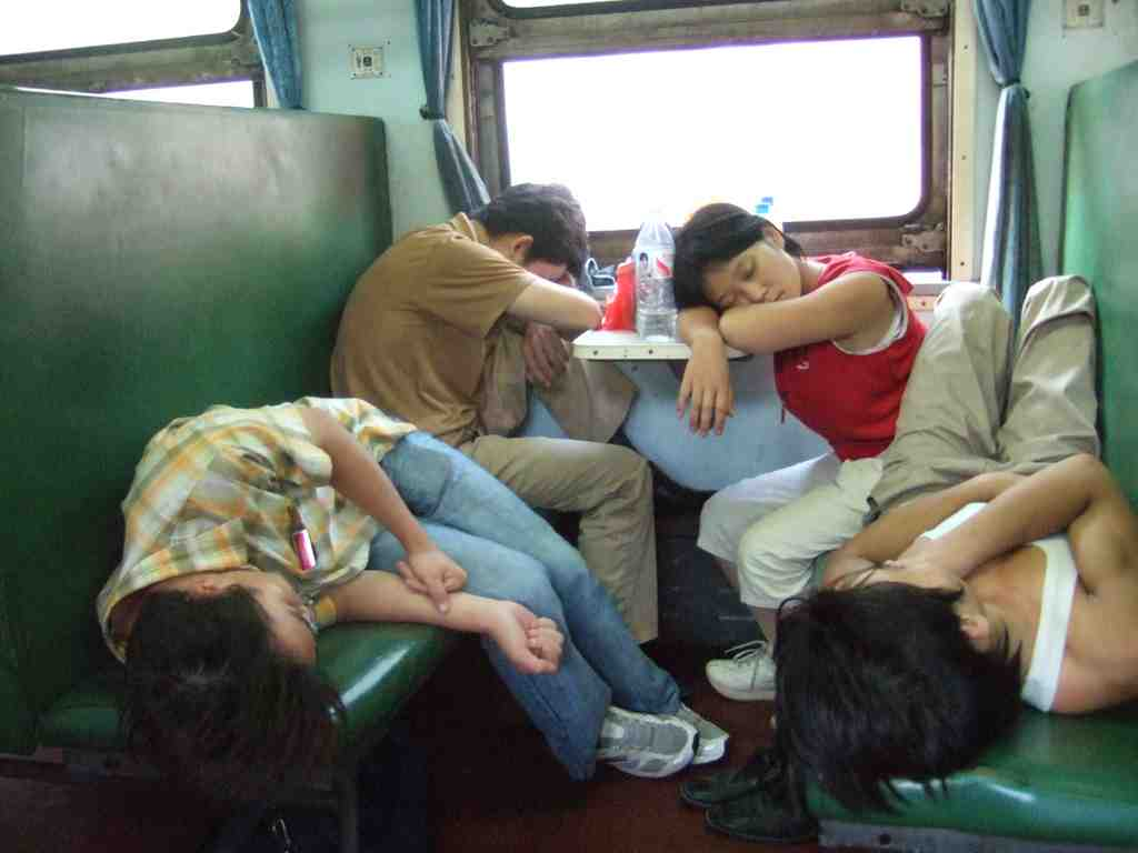 A Chinese family sleeping on hard seats on the bullet train