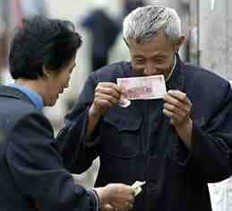 A Chinese man inspecting a Chinese bill to see if it's fake