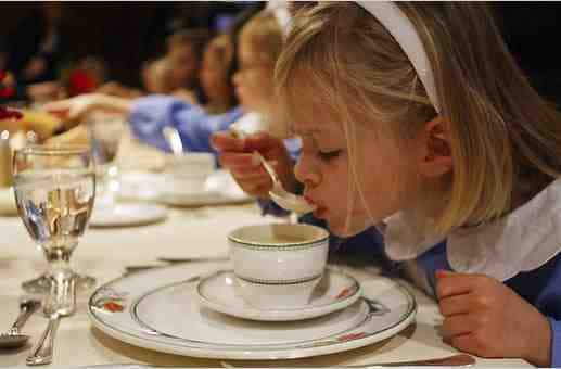 A young, blonde girl sipping on soup.