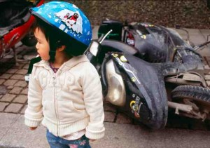 A little Chinese girl standing in front of a broken motorcycle