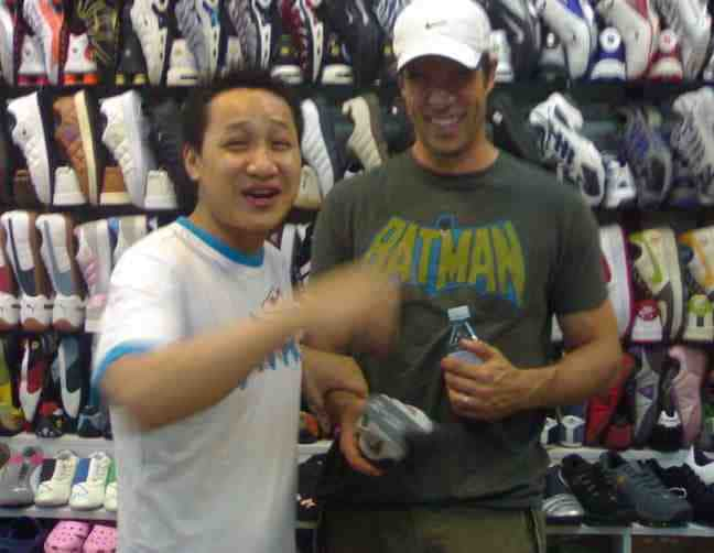 A foreigner doing his bargaining in China at a shoe store