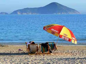 Two people sitting under an umbrella in beach chairs at Shek O Beach