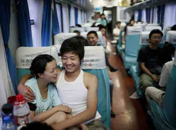 A Chinese couple sitting in soft seats on a bullet train