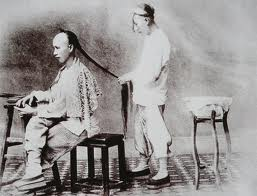 A historic photo of a Chinese man cutting another Chinese man's hair