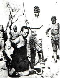 A Japanese soldier in position to behead a Chinese man