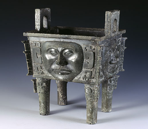 A Shang Dynasty bronze piece featuring a human mask