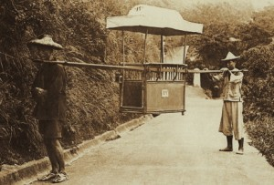 Two Chinese coolies holding an empty sedan chair