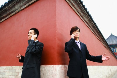 Two Chinese men talking at a wall
