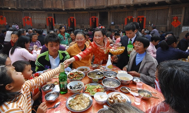 A Chinese bride toasts at a wedding table