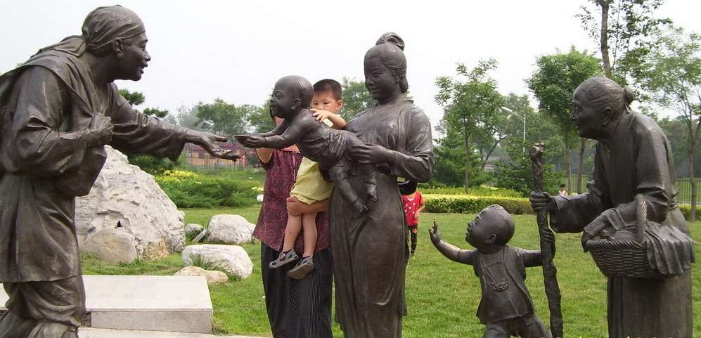 Chinese statues in a garden showing acts of friendship and kindness