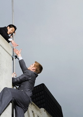 A man climbing a wall, looking for help