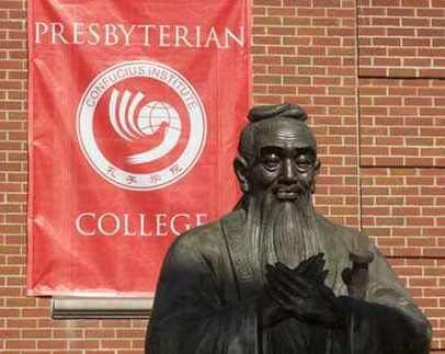 A statue of Confucius in front of a university banner