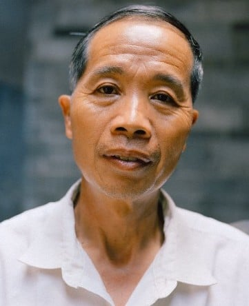 A Chinese man stares into a camera, not smiling.