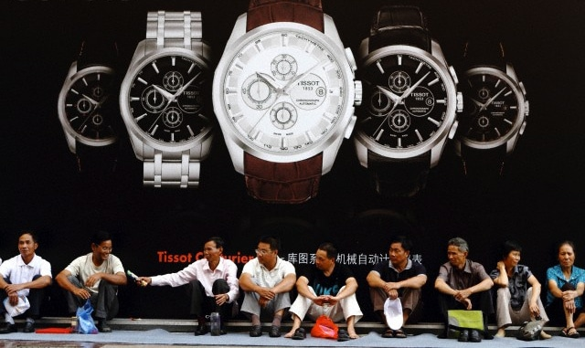 A group of Chinese men sitting in front of a fancy watch billboard