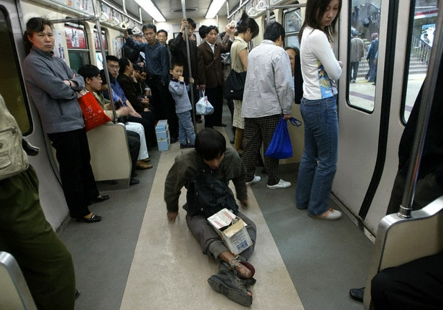 A homeless Chinese man sitting on the floor of a subway