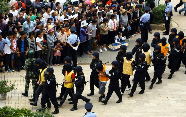 Chinese law officials escorting criminals