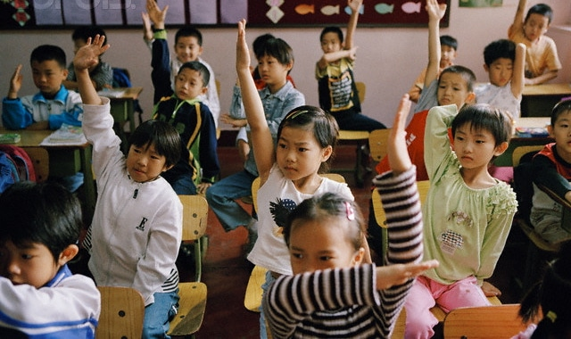 Young students in China raise their hands in the classroom.