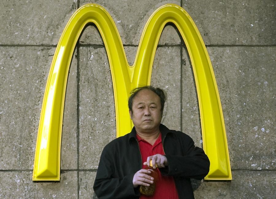 A Chinese man stands in front of a McDonalds sign, a symbol of obesity in China