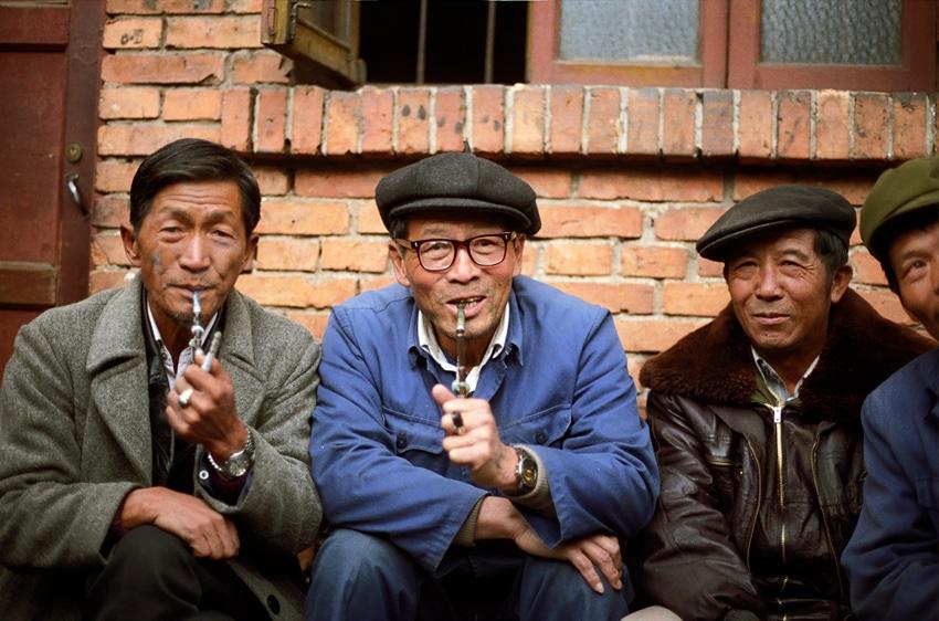 Chinese men sit together smoking