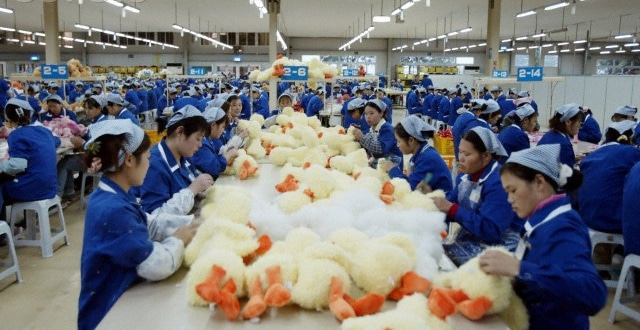 A group of Chinese people in a factory assembling stuffed toy ducks