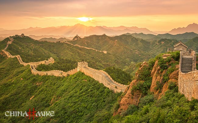 The Great Wall of China snaking through the mountains at sunset