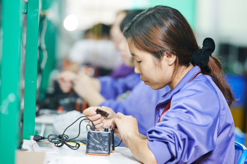 China woman assembling a part in a factory