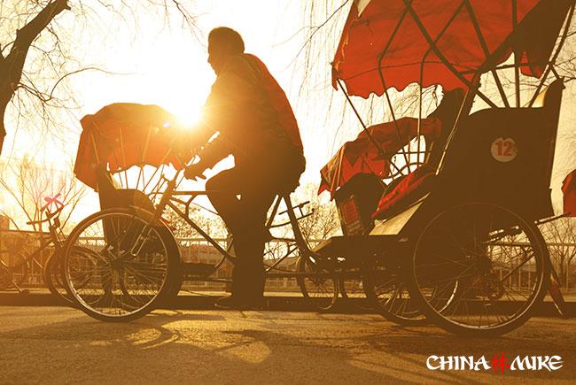 Rickshaw driver in China at dusk
