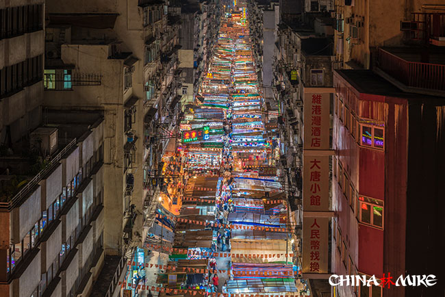 A street lit up with shopping signs in Hong Kong, China